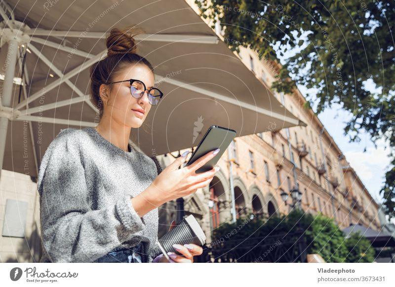 Junge stilvolle hübsche Frau mit Smartphone an der Outdoor-Café. jung Großstadt Internet Öffentlich Brille im Freien Porträt lässig Stil Lifestyle Mädchen