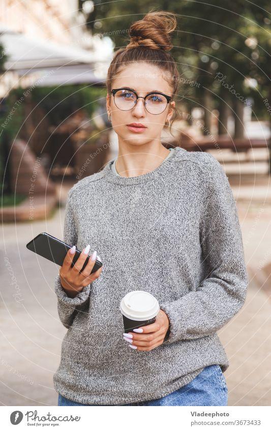 Junges Mädchen in Freizeitkleidung mit Smartphone und einer Tasse Kaffee zum Mitnehmen. Tägliches Leben der Jugend. Menschen online Frau jung Großstadt Internet