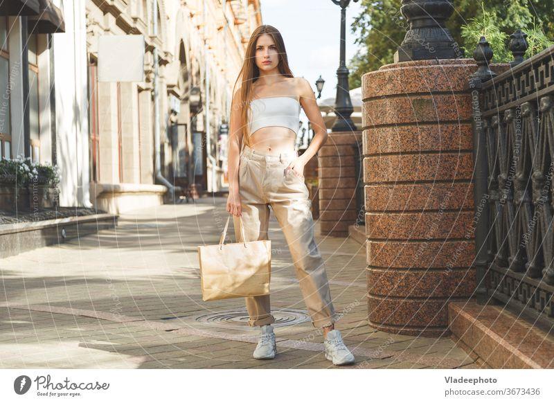 Schöne kaukasische modisch gekleidete Mädchen stehen im Freien mit Papiertüte mit Einkäufen in der Stadt. schön Mode Großstadt Tüte kaufen Frau jung Jeanshose