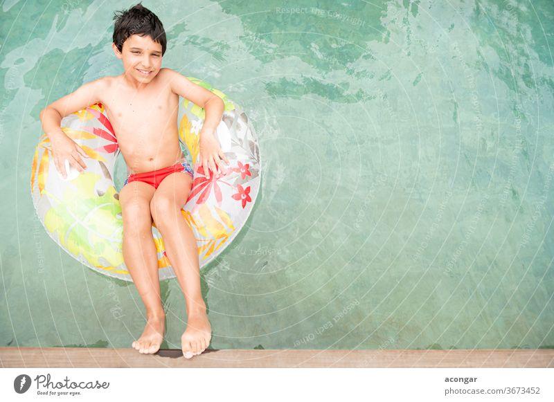 Junge, der auf einem aufblasbaren Kreis im Schwimmbecken schwimmt. Kind blau sorgenfrei Kaukasier Kindheit bequem cool niedlich Genuss Schwimmer Schwimmerrohr