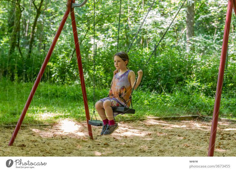Kleines Mädchen auf einer Schaukel im Wald Kind Spielen Freude Sommer Bewegung Spielplatz Kleinkind Fuß Motorik Schulhof Wiese Spieltrieb Kindheit Turnen Pause