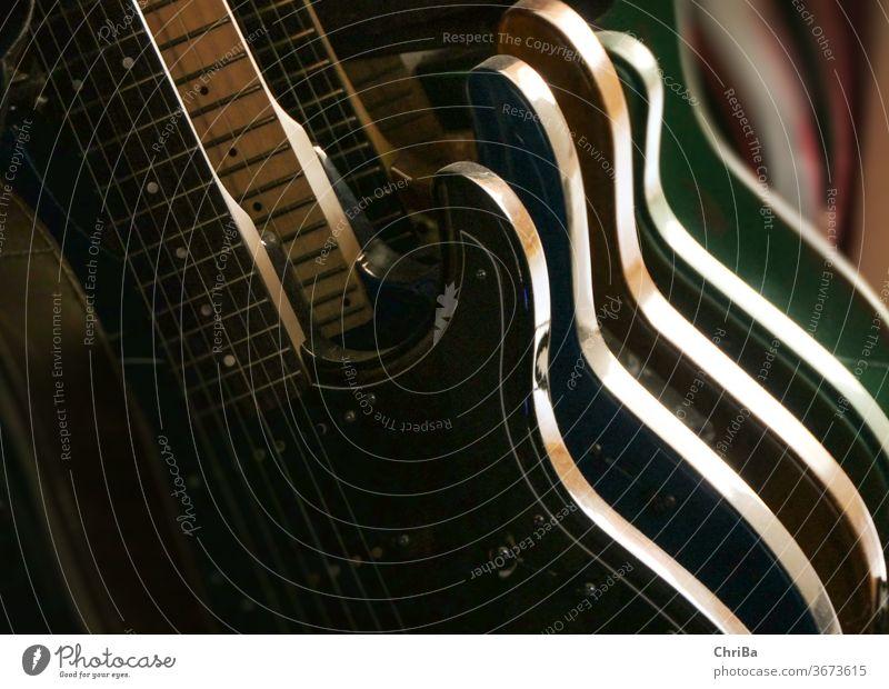 Gitarren im Ständer im Seitenlicht Gitarrenhals Gitarrenständer musik symbolisch gegenlicht streiflicht schatten gitarren Musikinstrument musizieren Klang Saite