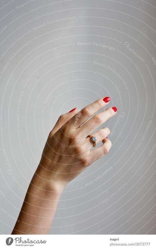 grazil | Rechte Hand einer jungen Frau mit Brillantring am Ringfinger und rot lackierten Fingernägeln vor neutralem Hintergrund. Junge Frau Stil zeigen schön