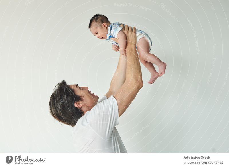 Vater hebt sein Baby hoch Familie Kind bald Junge Papa Spaß genießen heimwärts zu Hause zu Hause bleiben schön Model Porträt flach Menschen glückliche Familie