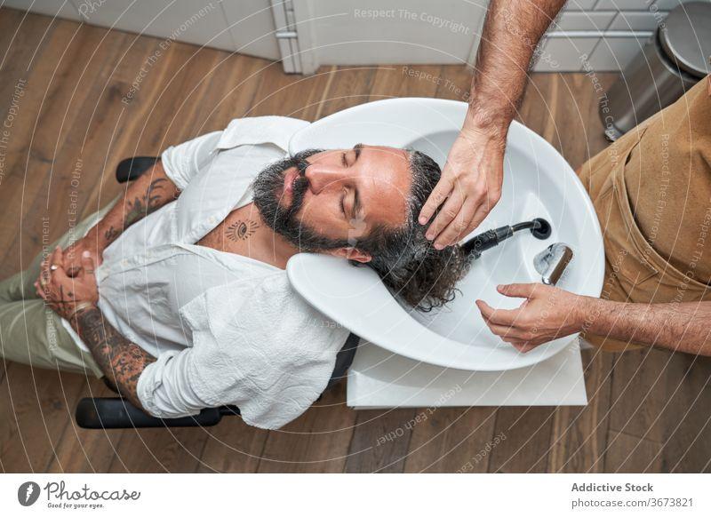 Friseur wäscht Haare eines männlichen Kunden im Salon Männer Kopf Waschbecken Barbershop Arbeitsplatz Klient Haarschnitt Dienst Vollbart Pflege professionell