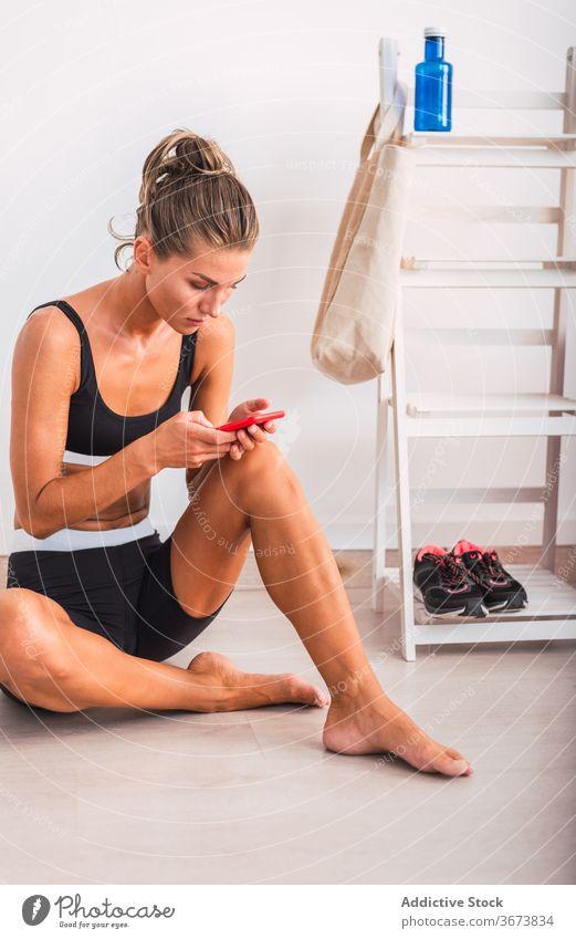 Sportlerin mit Smartphone nach dem Training müde Schweiß sich[Akk] entspannen benutzend Sportbekleidung intensiv Browsen Frau Funktelefon ruhen Wellness schlank