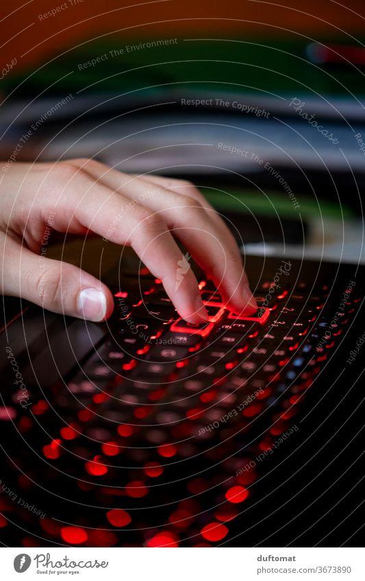 Hand auf beleuchteter Computer Tastatur Computerspiel Computer-Nutzer Teenager gamer Spielen Internet homeshopping shoppen online Onlineshop daddeln diabolisch