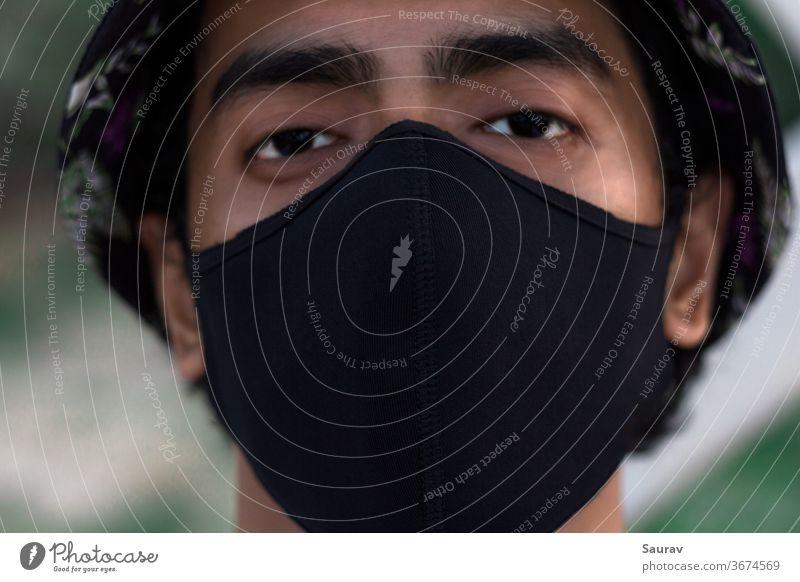 Nahaufnahme des Porträts eines jungen Jahrtausends, der eine schwarze Schutzmaske trägt, um eine Infektion mit dem Covid-19-Virus zu verhindern. Die neue Normalität während einer Weltpandemie.