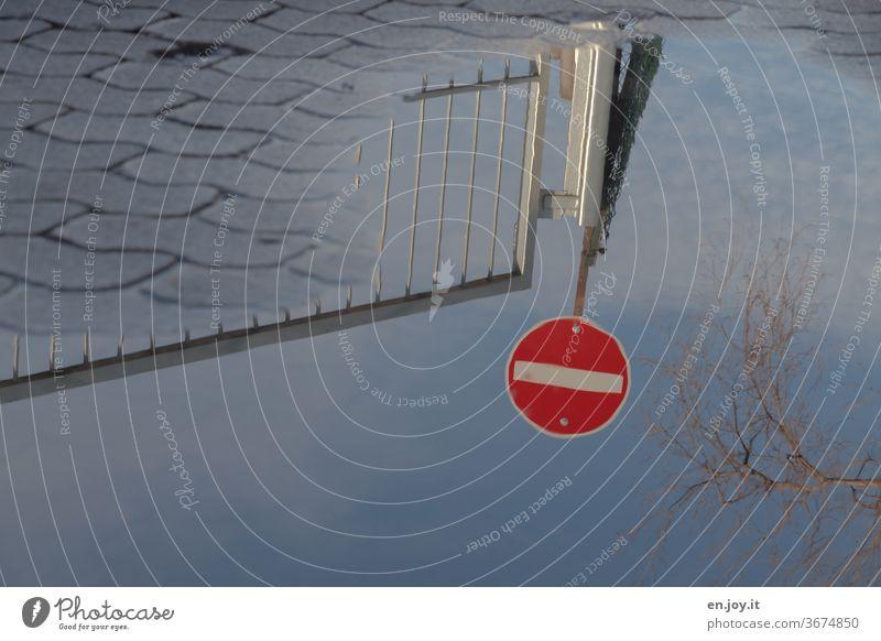 Spiegelung des Verkehrsschildes Verbot der Einfahrt in einer Wasserpfütze Schild Verbotsschild Durchfahrt verboten Pflastersteine Gehweg Zaun Tor Himmel