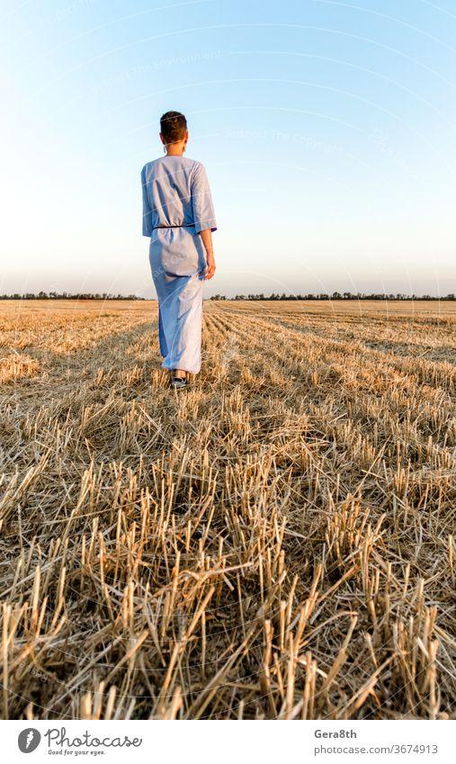 Eine Bäuerin geht durch ein gemähtes Weizenfeld in der Ukraine landwirtschaftlich Ackerbau authentisch Herbst Rücken blau Brot Bekleidung Land Landschaft Ernte