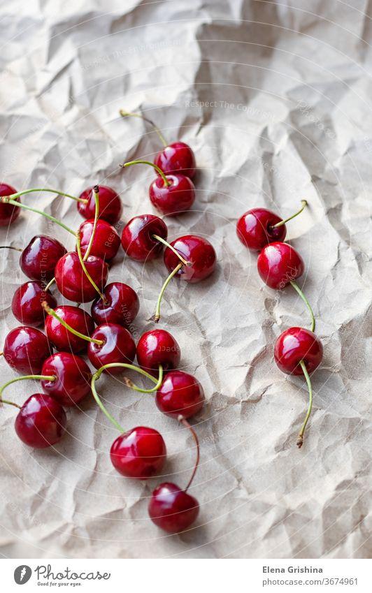 Beeren von reifen Kirschen auf einem Hintergrund aus Bastelpapier Süßkirsche rot Handwerk Papier frisch organisch Dessert süß Gesundheit Diät Sommer Frucht