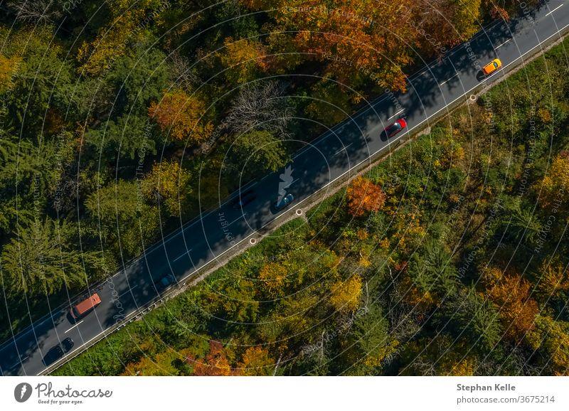 Vertikale Ansicht aus einer Drohne an einer Herbststraße. PKW Geschwindigkeit Dröhnen fallen diagonal inspirierend Straße Sonne Natur Landschaft fantastisch
