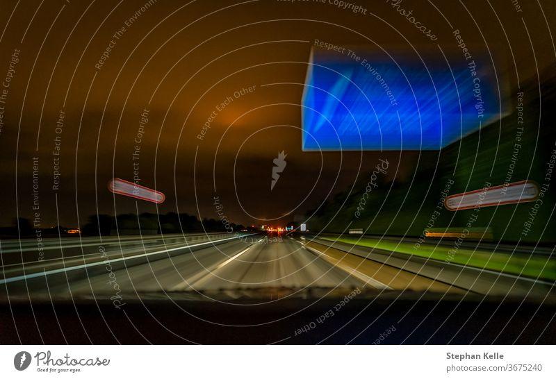 Die lang belichtete Aufnahme einer nächtlichen Autobahnfahrt bei schneller Fahrt über eine deutsche Autobahn und ein typisches blaues Schild. Licht Gebäude