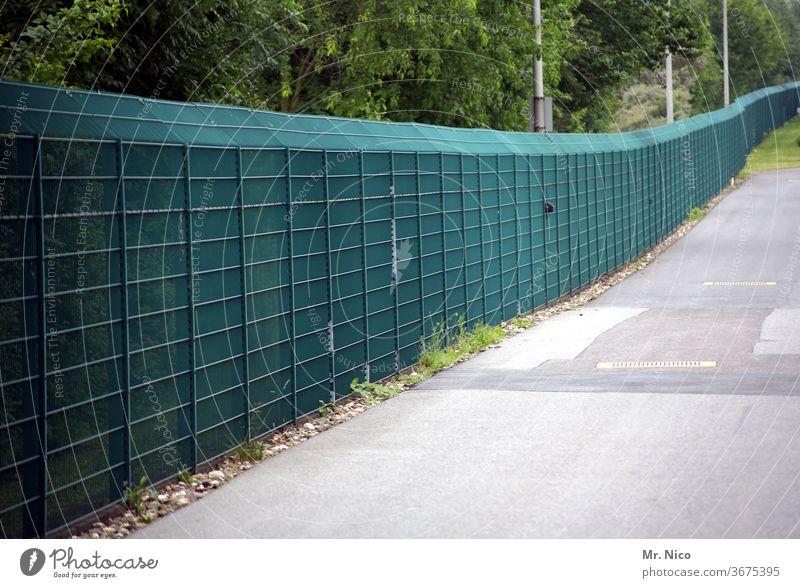 Ein langer grüner Zaun Barriere Sicherheit Absperrung gefangen bedrohlich Grenze Freiheit Schutz Flucht Ausgrenzen Gefangenschaft Verbote eingesperrt