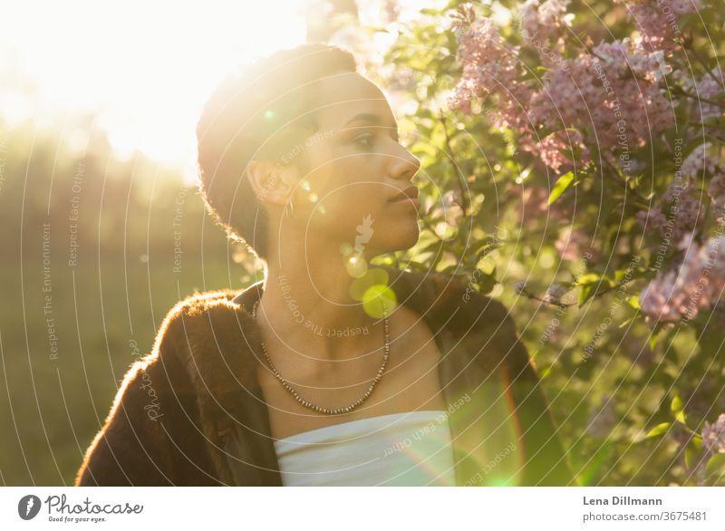 Frau vor Fliederbaum #4 junge Frau Mädchen Teenagermädchen draußen Natur Baum Strauch Fliederstrauch Sonne sonnig Sonnenlicht mixed afrodeutsch locken Mantel