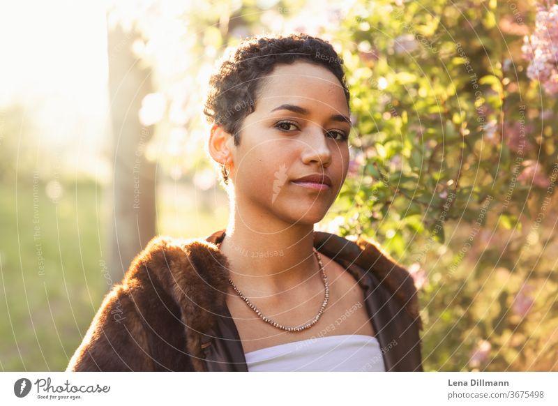 Frau vor Fliederbaum #3 junge Frau Mädchen Teenagermädchen draußen Natur Baum Strauch Fliederstrauch Sonne sonnig Sonnenlicht mixed afrodeutsch locken Mantel