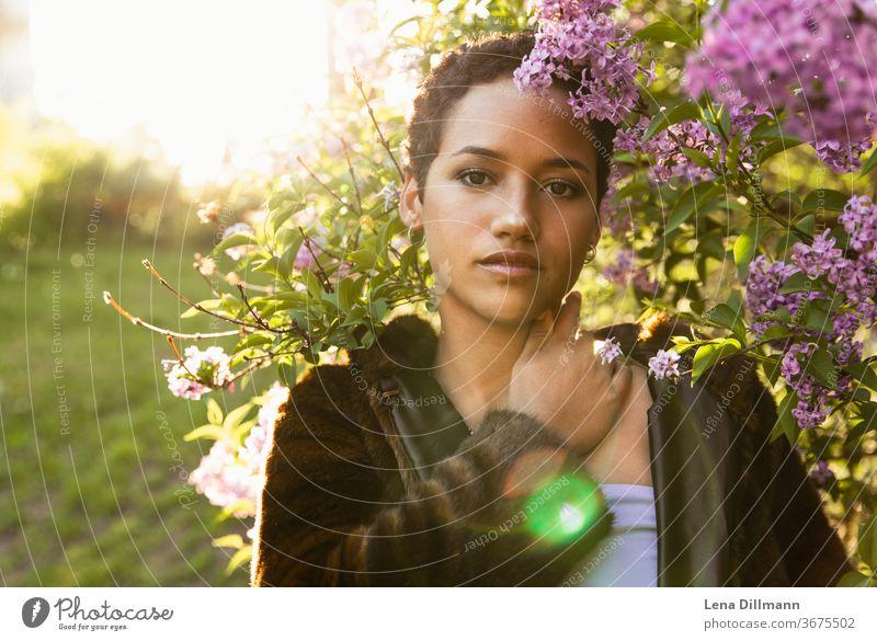 Frau vor Fliederbaum #2 junge Frau Mädchen Teenagermädchen draußen Natur Baum Strauch Fliederstrauch Sonne sonnig Sonnenlicht mixed afrodeutsch locken Mantel