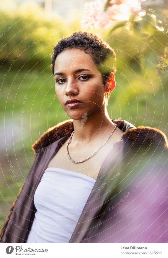 Frau vor Fliederbaum #1 junge Frau Mädchen Teenagermädchen draußen Natur Baum Strauch Fliederstrauch Sonne sonnig Sonnenlicht mixed afrodeutsch locken Mantel