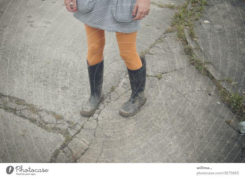 Nagellack und Gummistiefel Beine Mädchen dreckig gelbe Strümpfe Rock Straße stehen Rocktaschen Matschfestival Tristesse einsam warten junges Mädchen Kleid