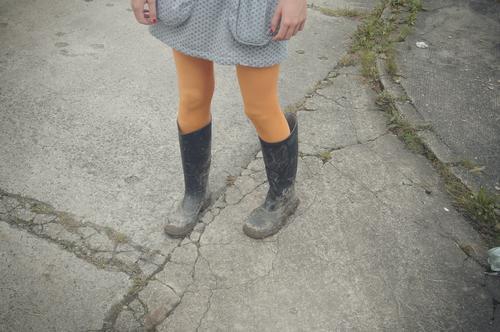 nagellack und gummistiefel Beine Mädchen Gummistiefel Nagellack dreckig gelbe Strümpfe Rock Straße stehen Rocktaschen Matschfestival Tristesse einsam warten