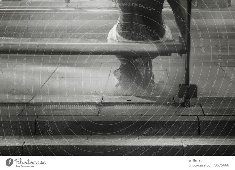 der haltestellenblues Haltestelle Bank Mensch Person sitzen warten trist grau öde langweilig Langeweile Mann Einsamkeit Öffentlicher Personennahverkehr Glaswand