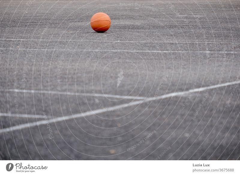 Ein vergessener Ball liegt im Abendlicht auf dem leeren Sportplatz Ballsport Spielen Freizeit & Hobby Farbfoto Außenaufnahme Menschenleer Sportstätten orange