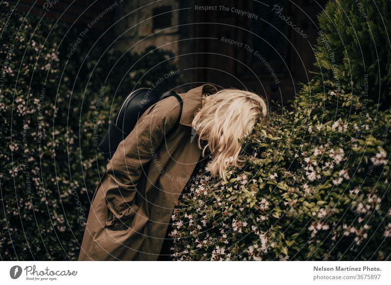 Porträt einer schönen stilvollen Blondine. Sie trägt einen grünen Mantel. Sie ist im Busch gebückt. Buchse aussruhen Mode verirrt blond stylisch gebogen