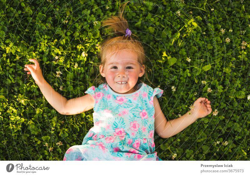 Hübsches kleines Mädchen liegt lachend im Gras und schaut auf. Baby Kindheit 2-3 happines bezaubernd niedlich Natur Lachender Spaß Gefühle Lächeln