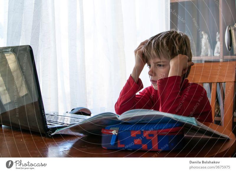 Schulkind in Selbstisolation mit Laptop für Hausaufgaben, Sozialer Fernunterricht im Online-Unterricht während der Coronavirus-Epidemie. Süßer Junge lernt und macht zu Hause während der Quarantäne seine Hausaufgaben