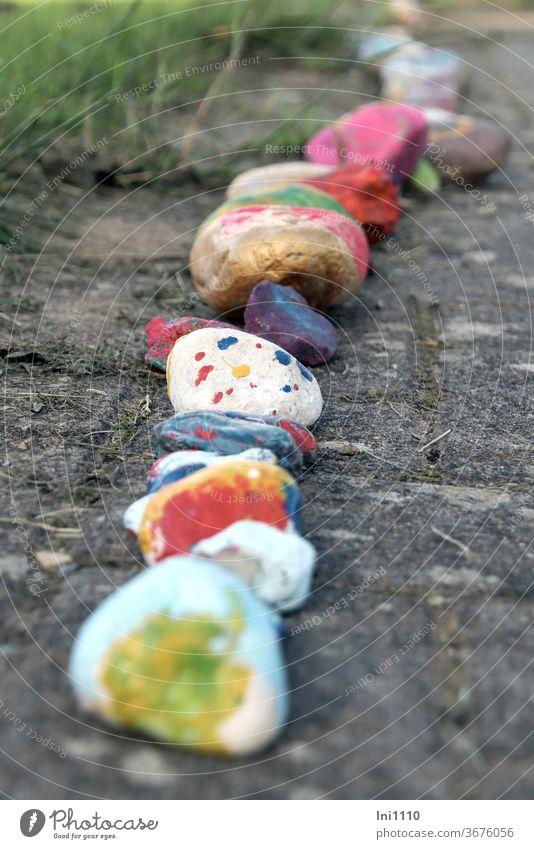 in Reihe ausgelegte bunt bemalte Glückssteine Stein Glücksbringer kleine Kunstwerke Natur Trend Ideen Hobby lächeln basteln Zeitvertreib verschenken