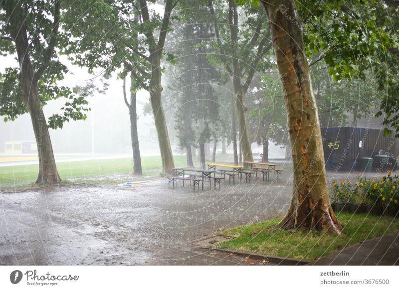Regen regen wetter schauer sommerregen biergarten leer menschenleer bank tisch möbel gartenmöbel klapptisch klappbank platz baum pfütze verregnet regenschauer