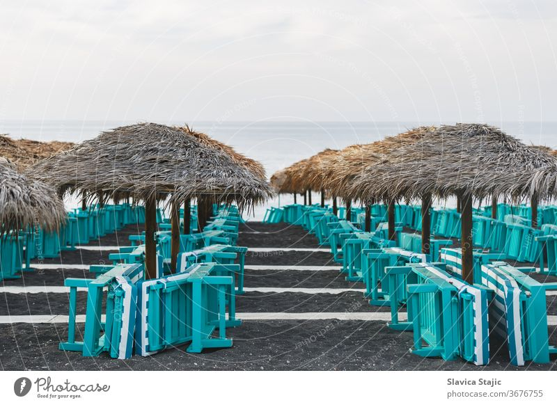Sonnenbänke und Sonnenschirme auf blankem Sandstrand. Perissa, Insel Santorin, Griechenland ägäisch Strand Strandpromenade schwarz blau Caldera Küste