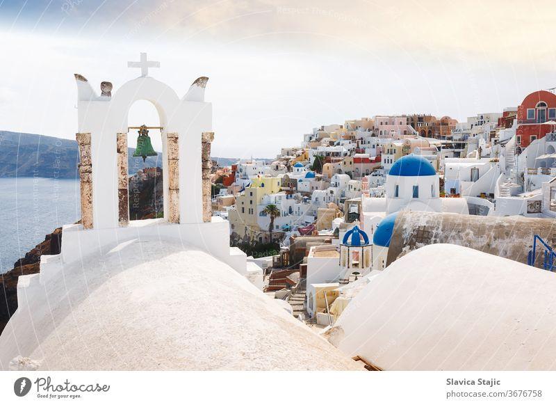 Blick auf das Meer und das Dorf Oia durch den traditionellen griechischen weißen Kirchenbogen mit Kreuz und Glocken im Dorf Oia auf der Kykladeninsel Santorin