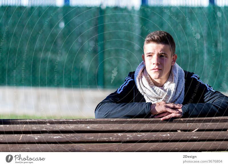 Attraktiver junger Mann im Stadtpark, der sich auf eine Holzbank lehnt und dabei wegschaut 1 Bank Lifestyle Erwachsener Typ Menschen Porträt männlich im Freien