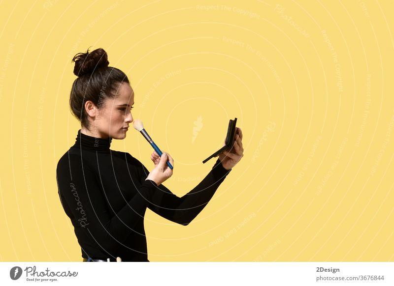 Seitenansicht einer jungen Frau mit Pferdeschwanz, die das Telefon als Spiegel benutzt, während sie Schminkpinsel auf die Gesichtshaut aufträgt Sitzen im Freien