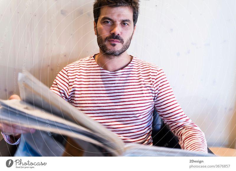Erwachsener Mann beim Zeitungslesen auf dem Sofa sitzend 1 männlich Menschen Nachrichten im Innenbereich Lifestyle Kaukasier Business Vollbart Sitzen Porträt