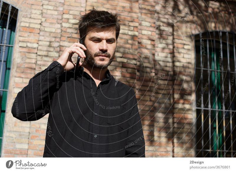 Junger bärtiger Mann mit Sonnenbrille und Jeanshemd steht auf der Straße der Stadt und spricht mit seinem Handy. Telefon Freizeitkleidung Lifestyle 1 männlich