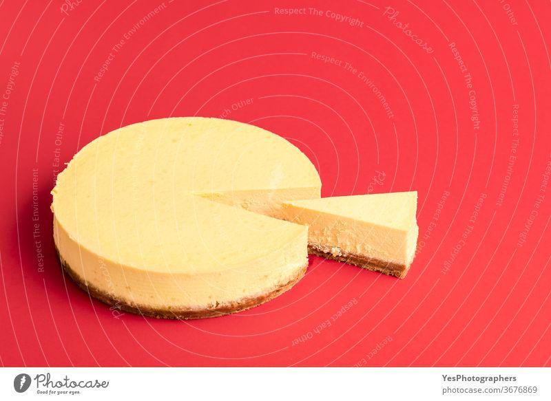 Klassischer Käsekuchen mit einem geschnittenen Stück. Scheibe cremiger Käsekuchen Hintergrund gebacken Bäckerei Frühstück Kuchen Weihnachten klassisch