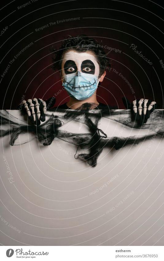 Happy Halloween. Kind mit medizinischer Maske in einem Skelettkostüm, das ein leeres Brett hält medizinische Maske Coronavirus covid-19 Party Spaß Schädel
