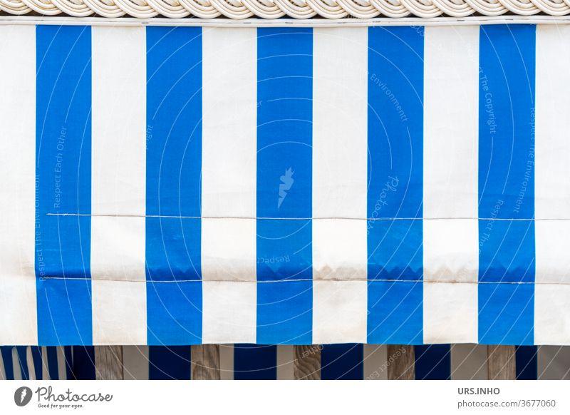 der blau weiß gestreifte Sonnenschutz am leeren Strandkorb verdeckt den Einblick Strandkorbvermietung sonnenschutz Dekor Sonnenblende Streifen