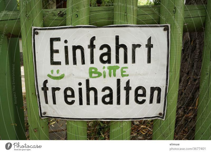 """""""Einfahrt BITTE freihalten"""" steht auf einem zerbeulten Metallschild an einem grünen Holzlattenzaun Einfahrt freihalten Bitte Schild Wunsch Zaun Holzzaun Smiley"""