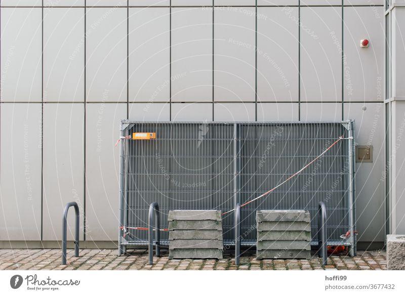 abgesperrte Bauzaungitter an einer Aussenfassade Absperrgitter Metallzaun Absperrung Gitterzaun Sicherheit Zäune abstrakt Flatterband graue Wand Fassade Linie
