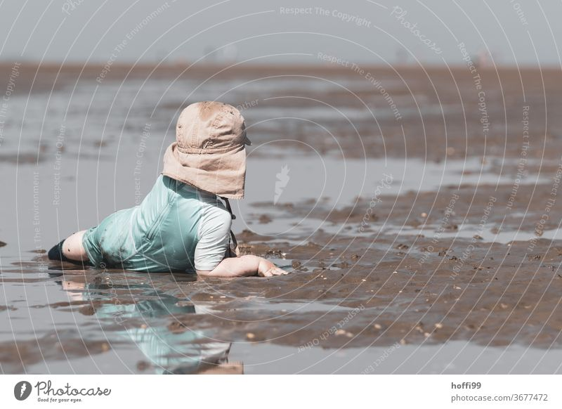 der kleine Junge liegt bequem im Watt und schaut sich um Kleinkind Kind Spielen Strand Wattenmeer Ebbe Nordsee Meer Küste Wasser Horizont Sommer Gezeiten