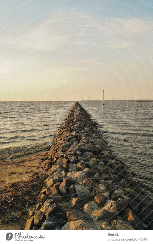 Wellenbrecher an der Nordsee in Harlesiel Meer Ebbe Flut Wasser Schlick Steine Carolinensiel Ostfriesland Küste Hafenschutz Molen Strand Urlaubsort
