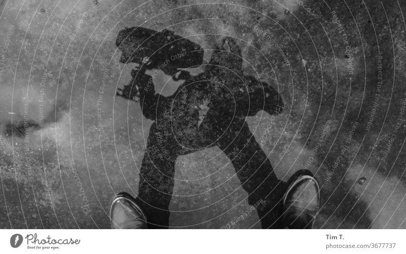 Mädchen mit Gitarre Pfütze Spiegelung Pfützenspiegelung Reflexion & Spiegelung Wasser Außenaufnahme nass Asphalt Tag Musikerin grau Frau Schuhe Schwarzweißfoto