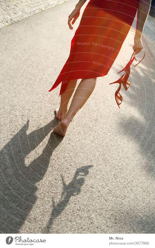 Frau in einem roten Kleid geht barfuß über die Straße Schuhe ausziehen Sommerkleid Barfuß Beine Fuß Damenschuhe Haut Wade Asphalt Stöckelschuh festhalten