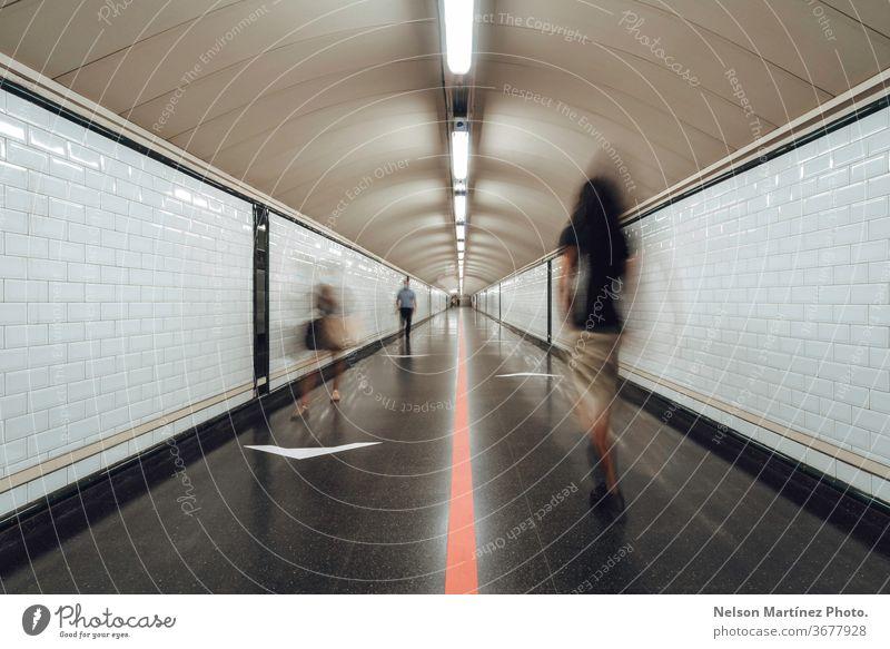 Verschwommene Personen, die in einem großen Tunnel eines Bahnhofs gehen. Die neue Normalität. Eine Gruppe von Menschen, die durch einen U-Bahn-Korridor eilt.