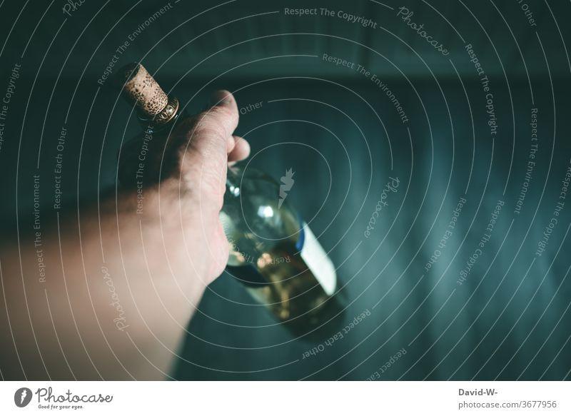 Mann hält eine Flasche Wein / Alkohol in der Hand Alkohol ist auch keine Lösung Säufer Sucht Alkoholsucht Alkoholisiert Alkoholiker Trinker düster dunkel