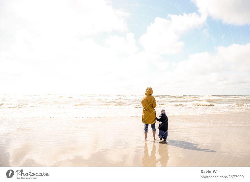 Mutter und Kind am Strand alleinerziehend zusammen zusammenhalt Mutter mit Kind gemeinsam Urlaub Eltern Familie Sonnenlicht Rückansicht zwei personen