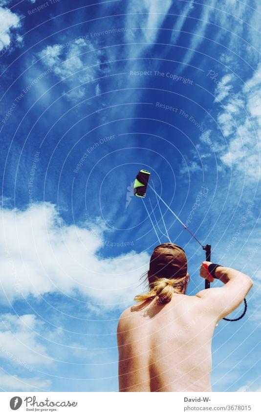 Mann lässt bei Bombenwetter einen Drachen steigen steigen lassen drachensteigen junger Mann Froschperspektive blau Himmel Wolken Sommer hobby Wind Spielen Luft